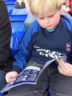Alex reading the programme
